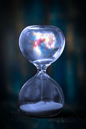 Space and galaxy in hourglass. Life time passing concept. Sand running through the bulbs of hourglass measuring passing time in a countdown to a deadline