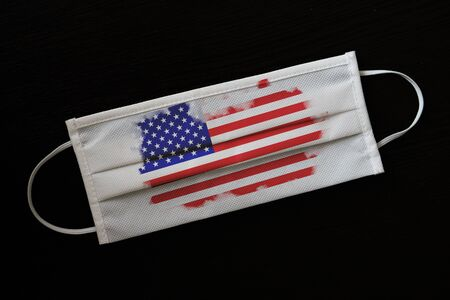 Medical mask with the image of the flag of the United States. Concept of the NCOV-19 coronavirus pandemic. Global threat to the countrys population