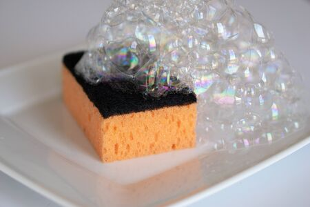 Foam sponge for washing dishes, white plate on a white background with foam Stock fotó