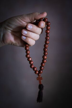 womans hand with wooden rosary or prayer beads.