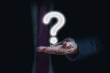 Businessman on blurred background question mark with his palm. Asking for answer or help.