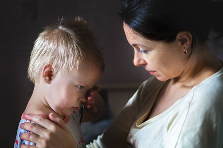 Tired mother hugging and calming little cute sad upset crying caucasian blond toddler boy at home indoor. Mom holding sleepy sick son. Child health, love and care concept.