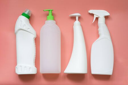 4 types of plastic bottles for household chemicals. Packaging for liquids. Empty, clean white plastic containers. Top view on a pink pastel background