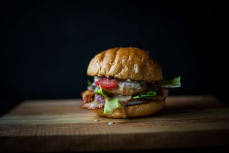 fresh tasty burger on black background. Delicious fresh homemade burger on a wooden table Stock fotó