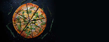 Tasty fresh baked pizza with tomatoes and basil on black background. Top view of hot delicious pizza. With copy space for text. Flat lay. Banner Stock fotó