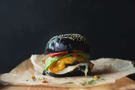 black hamburger on a wooden board on black background