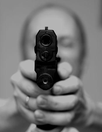 attacked: Man with a gun.Old man pointing a gun towards the camera.
