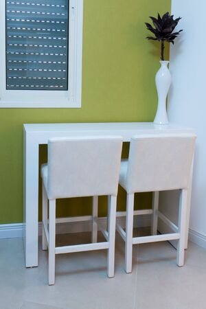 White table and chairs and a vase on the table in the kitchen photo