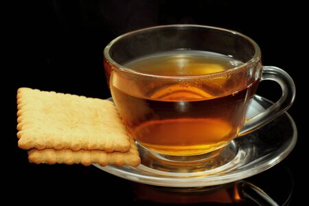 Cup of tea with biscuits on black background