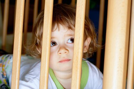 Sad little boy lying in a cage photo