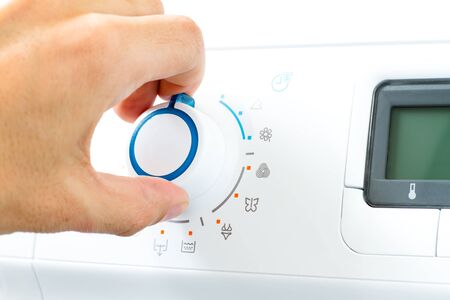 Hand Turning Washing Machine Appliance Dial photo