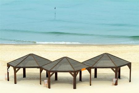 sunshades:  Three  sunshades on the beach.