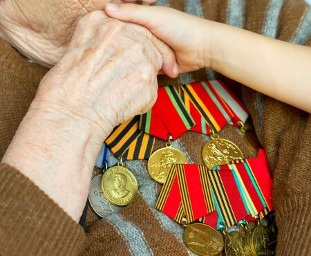 Grandmother kisses the hand of his grandson. Veteran of World War 2 Stock Photo - 13635844