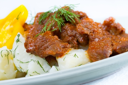 Beef stroganoff over boiled potatoes with pepper and dill Imagens