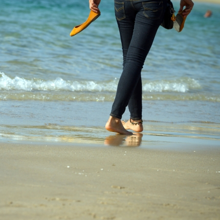 women in jeans: Young woman walking on a beach