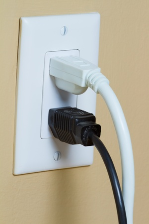 power cables: Two Electric black and white cable in Electrical Outlet on the Wall Stock Photo