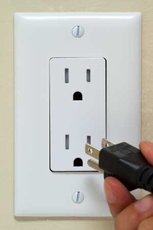 Electric cable on the hand and Electrical Outlet on the Wall photo