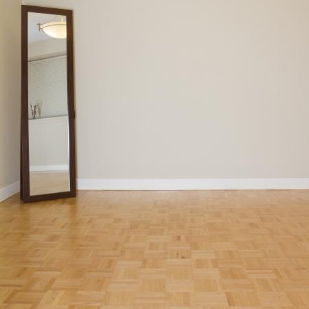 parquet floors: Soggiorno vuota con specchio in un nuovo appartamento