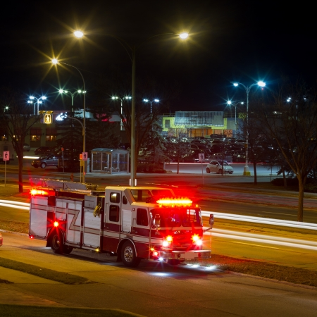 red siren: Firetruck is on the side of the road at night in the city  Editorial