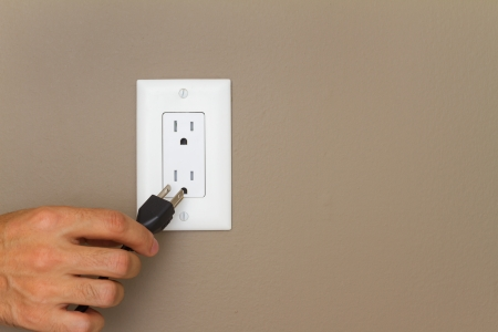 black appliances: Electric cable with hand and Electrical Outlet on the Wall. Power 110v