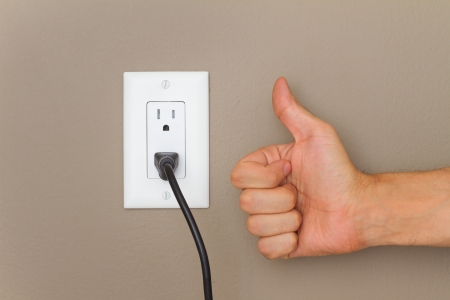 Thumbs up, and Electric cable in Electrical Outlet on the Wall. Power 110v  photo