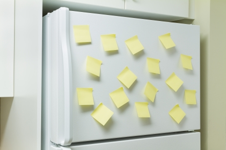 Blank yellow memory pages taped to a refrigerator door photo
