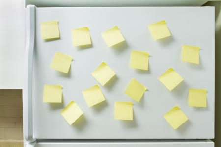 refrigerator: Blank yellow memory pages taped to a refrigerator door