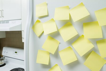 fridge: Blank yellow memory pages taped to a refrigerator door