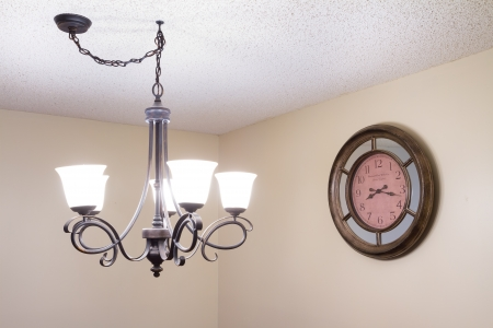 Old ceiling lamp and old clock in a new house  photo