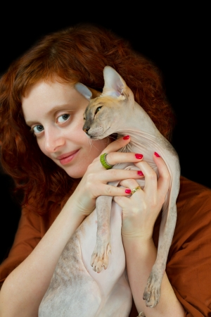 Portrait of red-haired girl with a Sphynx cat  photo