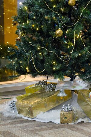 Decorated Christmas tree and boxes with gifts photo