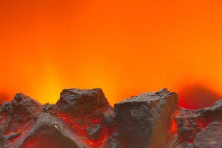 Electric fireplace with a burning coals and red-orange background photo