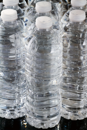 A row of plastic bottles of water on black background Stock Photo - 17102982