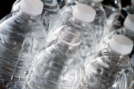 One open plastic bottle of water and other bottles closed on black background Stock Photo - 17102966