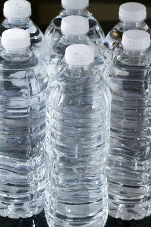 A row of plastic bottles of water on black background Stock Photo - 17102980