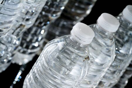 A row of plastic bottles of water on black background Stock Photo - 17102978