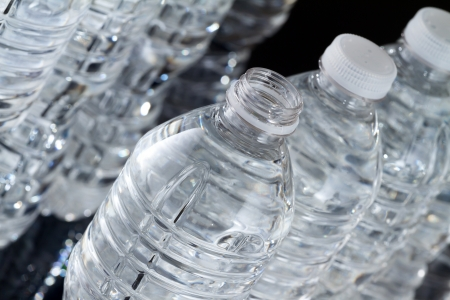 One open plastic bottle of water and other bottles closed on black background Stock Photo - 17126056