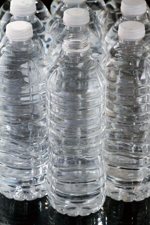 One open plastic bottle of water and other bottles closed on black background Stock Photo - 17158073