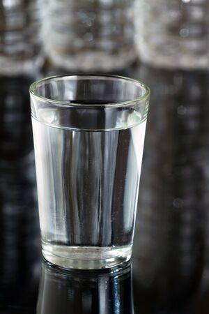 tomando refresco: Vidrio de agua en fondo botellas