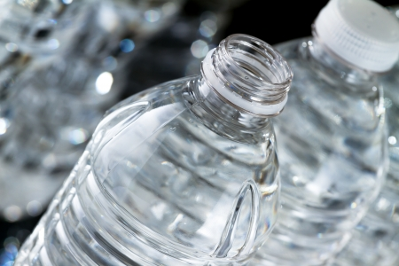 One open plastic bottle of water and other bottles closed on black background Stock Photo - 17158069