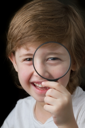 Cute little boy looking through a magnifying glass and smiling photo