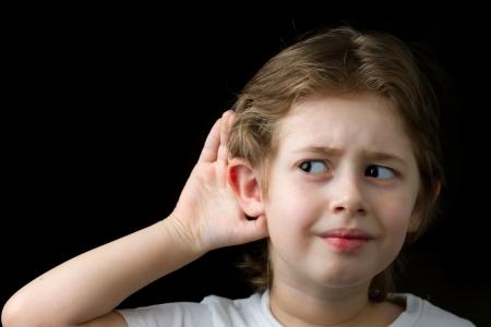 何かを聞くにしようとしている男の子 写真素材
