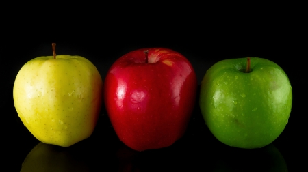 green background: Red, Yellow and Green Apple on a black background