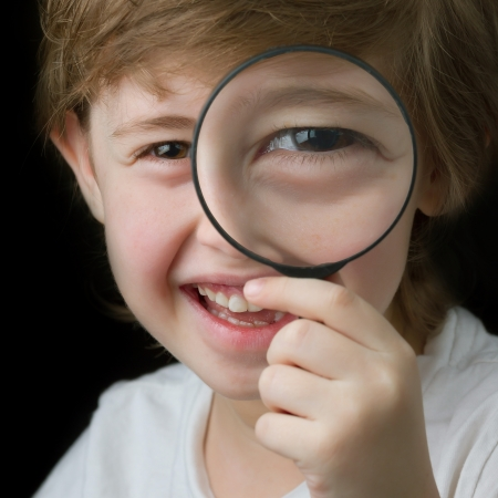 schoolkid search: Cute little boy looking through a magnifying glass and smiling