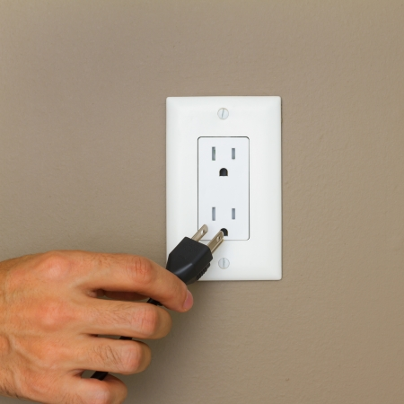 Electric cable with hand and Electrical Outlet on the Wall  Power 110v  photo