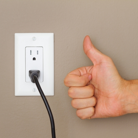 Thumbs up, and Electric cable in Electrical Outlet on the Wall  Power 110v  photo