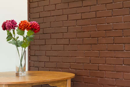 Vase with  flowers on the table and brick wall backgound photo