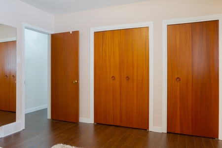 Wooden doors of the closets with mirror in the bedroom photo