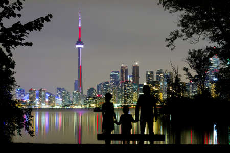 Silhouettes of family watching Toronto Downtown Skyline at night