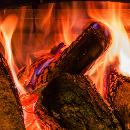 mantelpiece: Old fireplace with a burning firewoods Stock Photo